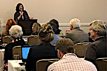 Adams | Stirling Partner Laurie S. Poole speaks before standing-room-only crowd